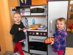 Girls playing at kitchen in dramatic play area
