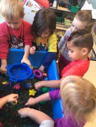 Children exploring a sensory tub full of water beads