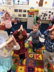 Children doing yoga in classroom