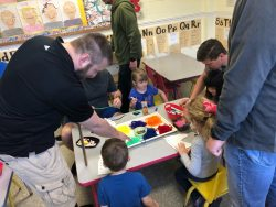 Children completing a craft with their dads