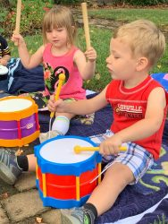 Children playing the drums outside