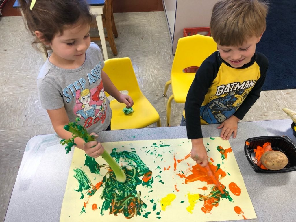 Children painting with raw vegetables