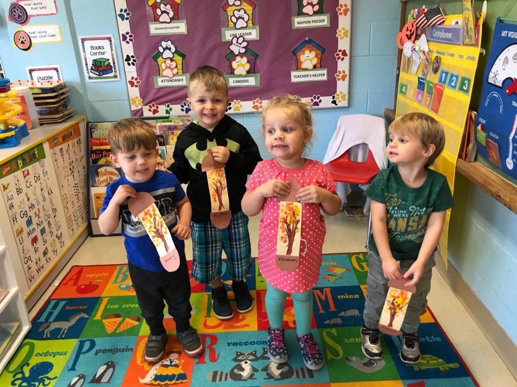 Children displaying their fall artwork